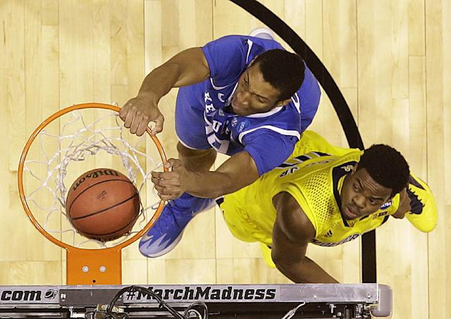 Kentucky's Marcus Lee dunks in front of Michigan's Derrick Walton Jr. during the first half of an NCAA Midwest Regional final college basketball tournament game Sunday, March 30, 2014, in Indianapolis. (AP Photo/David J. Phillip)