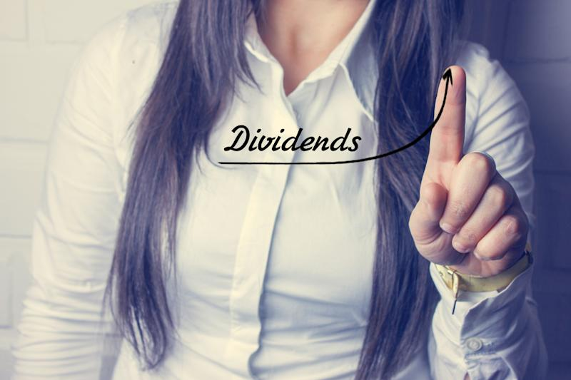 "A woman tracing a rising line under the word ""dividends."""