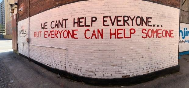 Highjinx says the mural on its building spreads a positive message about helping one another, but the City of Ottawa says it was painted without a permit and must be removed. (Submitted by Karen Nielsen  - image credit)