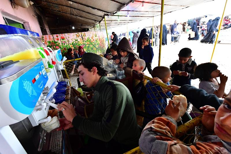 Children buy ice cream from a shop in a market at Al-Hol camp for displaced people in northeastern Syria