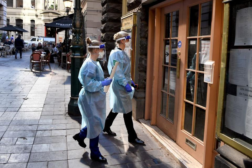 Health department officials arrive to inspect a restaurant and bar in Melbourne on May 12, 2021, after a man who had dined there later tested positive for Covid-19 in the first community case in the city for two months. (Photo by William WEST / AFP) (Photo by WILLIAM WEST/AFP via Getty Images)