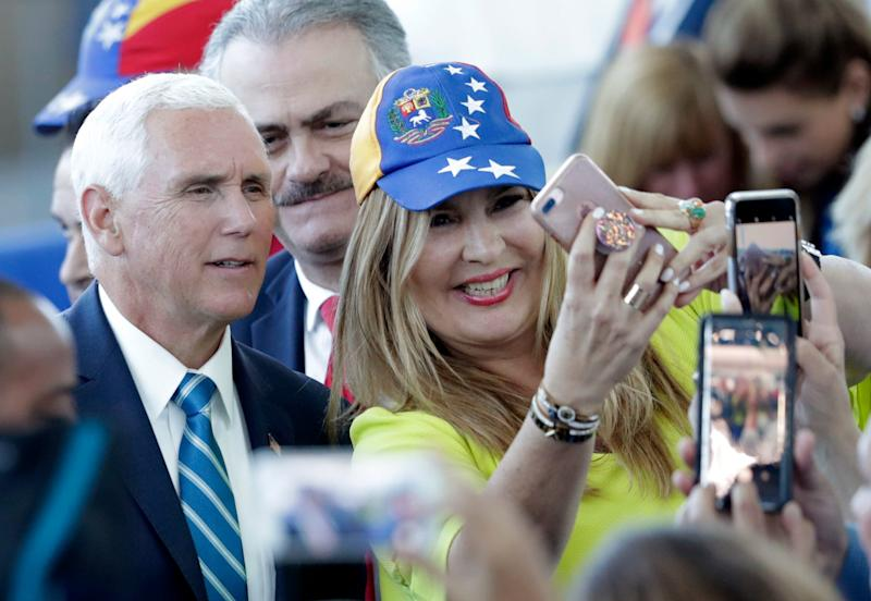 Vice President Mike Pence poses with Paula Tenreiro, who is wearing a cap with the design of the Venezuelan flag, following a tour on the USNS Comfort, Tuesday, June 18, 2019, in Miami.