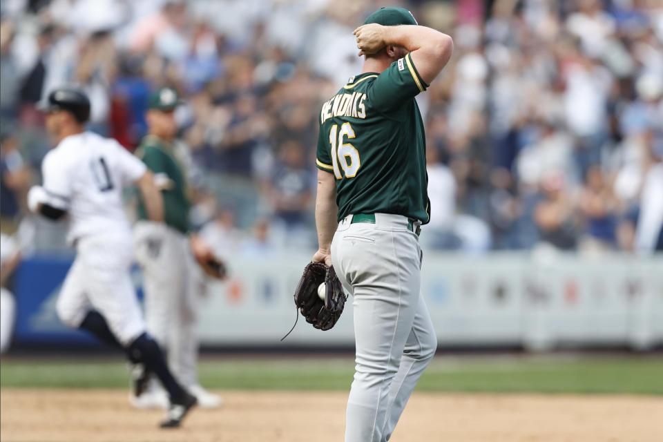 Oakland Athletics' relief pitcher Liam Hendriks (16) reacts after allowing a game-tying, solo home run to New York Yankees' Brett Gardner, left, who rounds the bases in the ninth inning of a baseball game, Sunday, Sept. 1, 2019, in New York. (AP Photo/Kathy Willens)