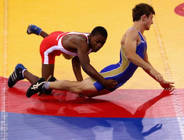 SINGAPORE - AUGUST 15: Artur Suleymanov of the Russian Federation competes against Jason Afrikaner of Namibia in the Men's Greco Roman 58kg Wrestling competition on day one of the Youth Olympics at the International Convention Centre on August 15, 2010 in Singapore. (Photo by Mark Dadswell/Getty Images)