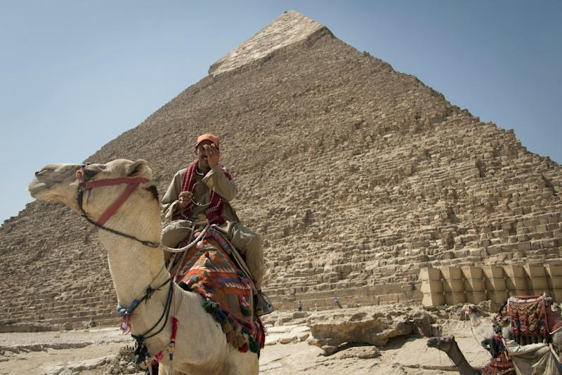 In this Thursday, Sept. 27, 2012 photo, a tour guide sits on his camel as he waits for clients next to the Giza pyramids, near Cairo, Egypt. The Egyptian demonstrations against an online film that was produced by a U.S. citizen originally from Egypt and denigrates the Prophet Muhammad were part of a wider explosion of anger in Muslim countries. They happened near the U.S. Embassy, far from the pyramids of Giza on Cairo's outskirts, and a lot further from gated Red Sea resorts, cocoons for the beach-bound vacationer. Yet the online or TV images _ flames, barricades, whooping demonstrators _ are a killjoy for anyone planning a getaway, even though the protests have largely subsided. Tour guides in Egypt say tourist bookings are mostly holding, but they worry about a dropoff early next year, since people tend to plan several months ahead.(AP Photo/Khalil Hamra)