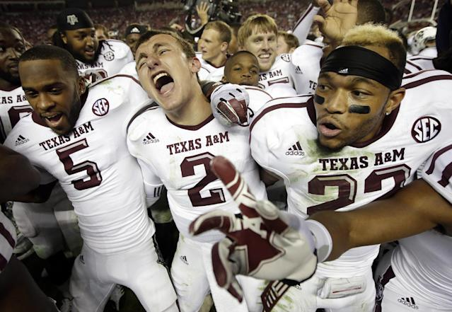 FILE - In this Nov. 10, 2012, Texas A&M quarterback Johnny Manziel (2) is joined by wide receiver Kenric McNeal (5) and defensive back Dustin Harris (22) as they celebrate a 29-24 win over top-ranked Alabama an NCAA college football game at Bryant-Denny Stadium in Tuscaloosa, Ala. The two teams meet again on Saturday, Sept. 14, 2013, in College Station, Texas. (AP Photo/Dave Martin, FIle)