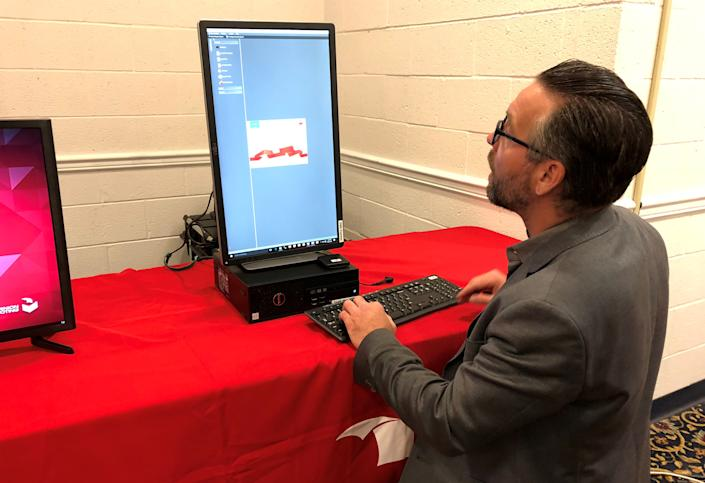 Eric Coomer demonstrates one of the company's voting machines, in Harrisburg, Pennsylvania, U.S., April 26, 2018. Picture taken April 26, 2018.  REUTERS/Sharon Bernstein