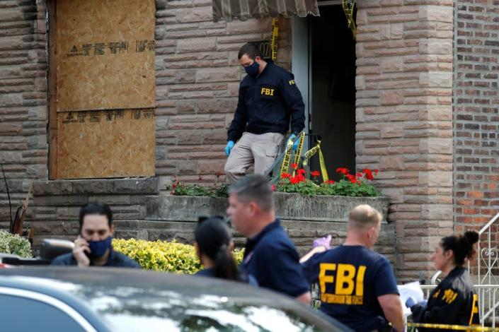FBI officers outside a house where police say bomb-making materials were found in New York