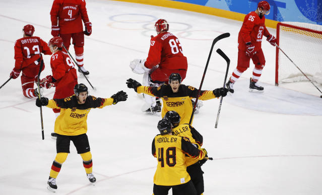 Dominik Kahun (72), of Germany, Frank Hrdler (48), Jonas Muller (41) and Frank Mauer (28) celebrate after a goal by Mueller during the third period of the men's gold medal hockey game against the Olympic athletes from Russia at the 2018 Winter Olympics, Sunday, Feb. 25, 2018, in Gangneung, South Korea. (AP Photo/Jae C. Hong)