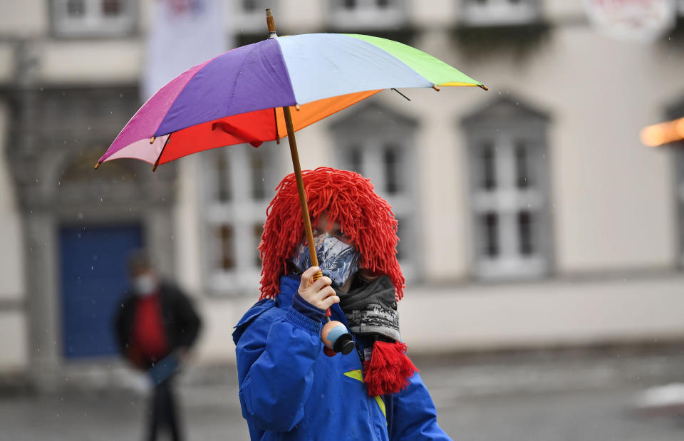 A young carnival reveller dressed as a clown holds an umbrella in the empty old town in Duesseldorf, Germany, Monday, Feb. 15, 2021. Because of the coronavirus pandemic the traditional; carnival parades are canceled but eight floats are pulled through the empty streets in Duesseldorf, where normally hundreds of thousands of people would celebrate the street carnival. (AP Photo/Martin Meissner)