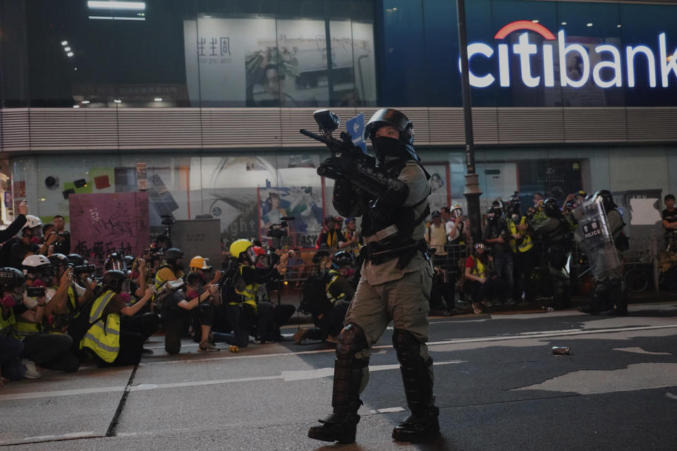 "A Hong Kong police officer holds a weapon during confrontation with protesters in Hong Kong Sunday, Oct. 27, 2019. Hong Kong police fired tear gas Sunday to disperse a rally called over concerns about police conduct in monthslong pro-democracy demonstrations, with protesters cursing the officers and calling them ""gangster cops."" (AP Photo/Vincent Yu)"