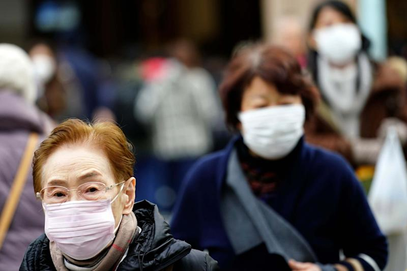 Pedestrians wear protective masks as they walk through a shopping district in Tokyo: AP