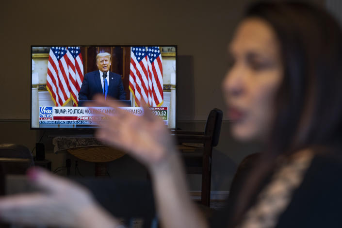 """Natalie Abbas works at her """"Command Post,"""" her dining room table, as she watches Fox News broadcast President Donald Trump's farewell address, in Myersville, Md., Tuesday, Jan. 19, 2021, the day before the presidential inauguration. As a member of Braver Angels, Abbas, who believes the election was stolen, meets regularly with a neighbor who cheers Biden as the rightful winner, to ponder the greatest challenge facing Biden and American society: how can they find common ground if they no longer exist in the same reality? (AP Photo/Cliff Owen)"""