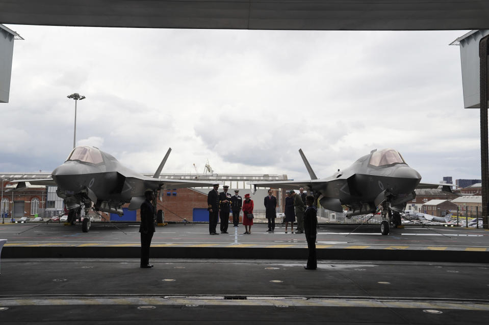 Britain's Queen Elizabeth II , cente stands on the flight deck, with a pair of F-35B Lightning II aircraft on either side, during a visit to HMS Queen Elizabeth at HM Naval Base, ahead of the ship's maiden deployment, in Portsmouth, England, Saturday May 22, 2021. HMS Queen Elizabeth will be leading a 28-week deployment to the Far East that Prime Minister Boris Johnson has insisted is not confrontational towards China. (Steve Parsons/Pool Photo via AP)
