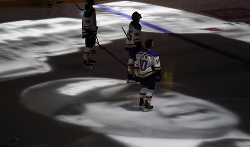 St. Louis Blues center Brayden Schenn stands on an image of former Colorado Avalanche president and general manager Pierre Lacroix projected onto the ice during a tribute Lacroix before an NHL hockey game, Wednesday, Jan. 13, 2021, in Denver. Lacroix died from complications of COVID-19 last month. (AP Photo/David Zalubowski)