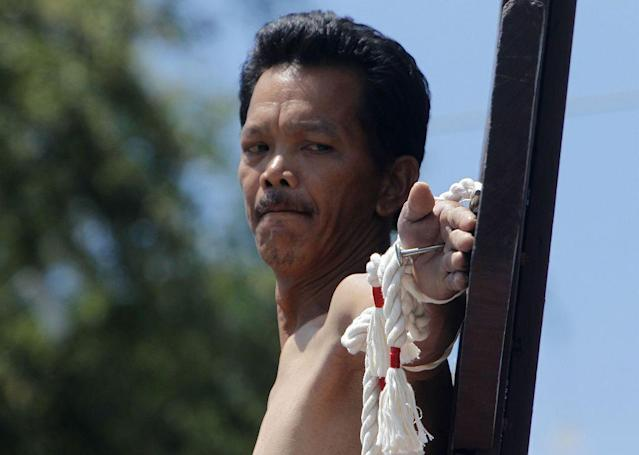 Renato Cunanan, who portrays Jesus Christ, looks at the nail in his palm on a wooden cross during a Good Friday crucifixion re-enactment in San Juan village, Pampanga province, north of Manila.