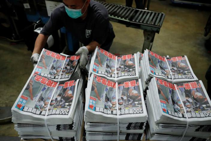 """Bundles of the Apple Daily newspaper, published by Next Media Ltd, with a headline """"Apple Daily will fight on"""" are seen at the company's printing facility in Hong Kong"""