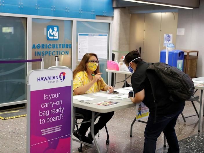 A traveler checks in with airport authorities at the Daniel K. Inouye International Airport during the spread of the coronavirus disease (COVID-19) in Honolulu, Hawaii, U.S., April 28, 2020. Picture taken April 28, 2020.