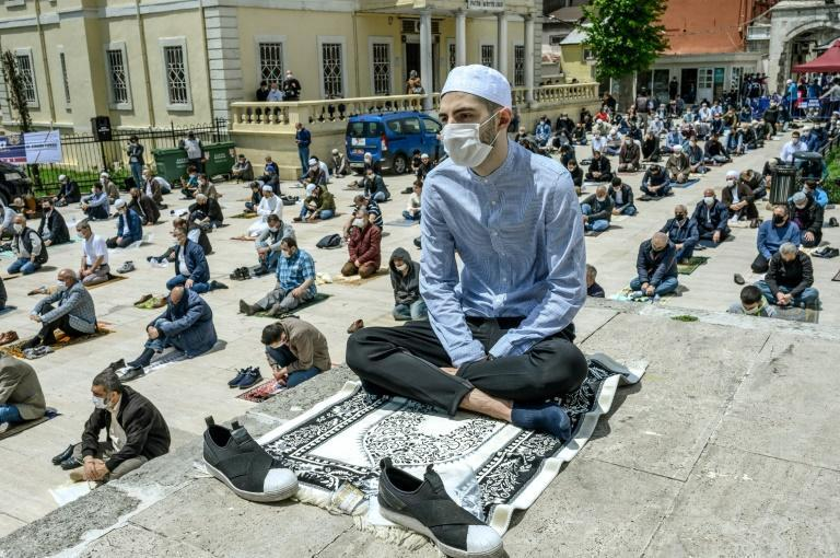 Worshippers wearing face masks maintain the required social distance during Friday prayers outside the reopened Fatih Mosque in Istanbul
