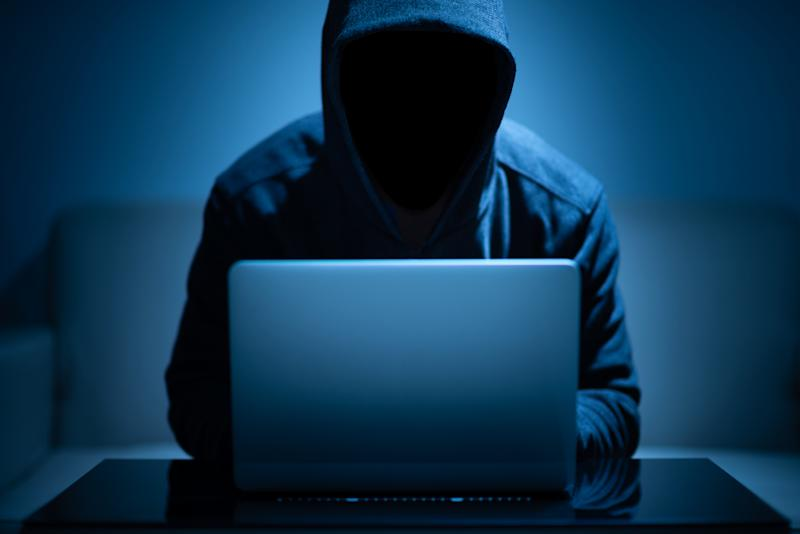 Hooded man using laptop in the dark room