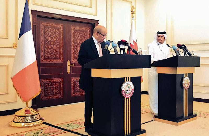 In this photo provided by the Qatar News Agency, French Foreign Minister Jean-Yves Le Drian, left, speaks during a news conference with his Qatari counterpart Mohammed bin Abdulrahman al-Thani in Doha, Qatar, Saturday, July 15, 2017. Le Drian called on Qatar's neighbors to immediately lift measures impacting thousands of people in the Gulf, becoming the latest foreign diplomat to visit the region and attempt to find a resolution to a crisis that has dragged on for more than a month. (Qatar News Agency via AP)