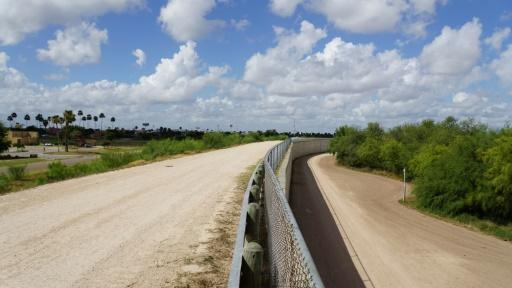 The border divide: a wall along one of the several layers of the US-Mexico border fencing in the border town of McAllen, Texas