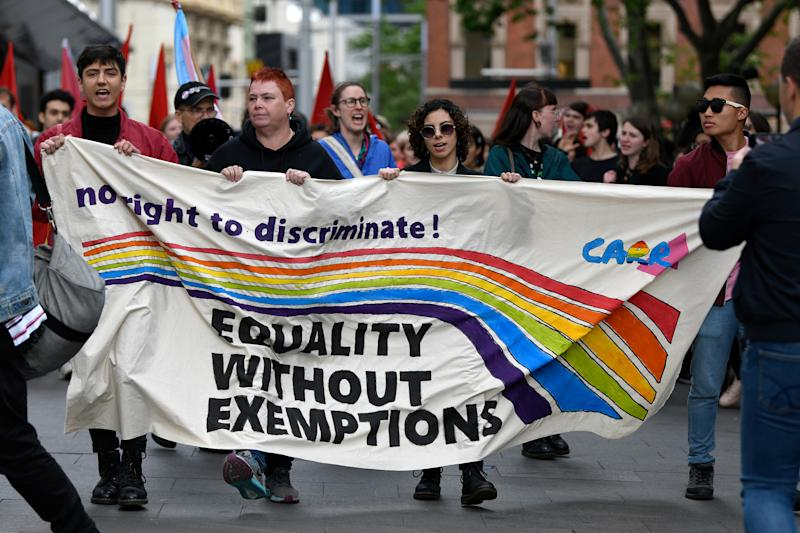 Protestors holding a banner are seen marching during a rally to protest against the Religious Discrimination Bill at Sydney Town Hall in Sydney.