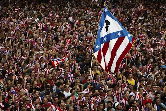 Atletico de Madrid supporters wave a flag with their team emblem as they celebrate the Spanish first division title ''La Liga'' with his team players at the Neptuno fountain in Madrid, Sunday May 18, 2014. A 1-1 draw against Barcelona on the last match gave Atletico its first La Liga title in 18 years. (AP Photo/Daniel Ochoa de Olza)