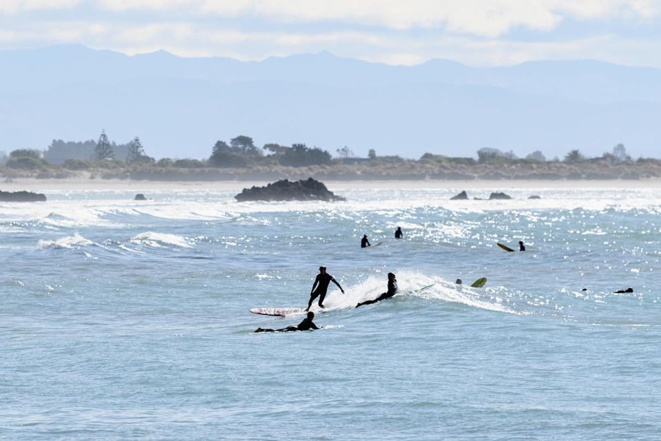 Surfers are seen at Scarborough Beach in Christchurch, New Zealand.