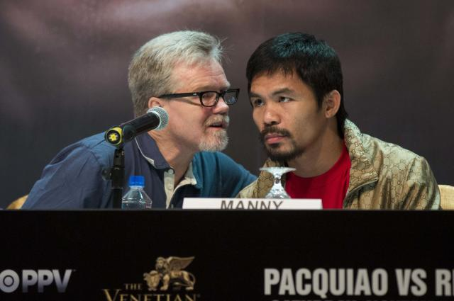 Filipino boxer Manny Pacquiao listens to his coach Freddie Roach (L) during a news conference at the Venetian Macao hotel in Macau November 20, 2013. Pacquiao will fight against American Brandon Rios in a 12-round welterweight clash on November 24. REUTERS/Tyrone Siu (CHINA - Tags: SPORT BOXING)