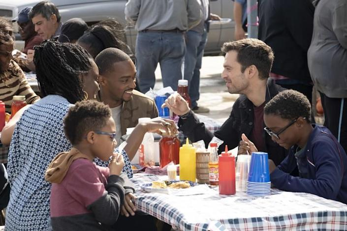 A woman, two men and two boys smiling at a picnic table
