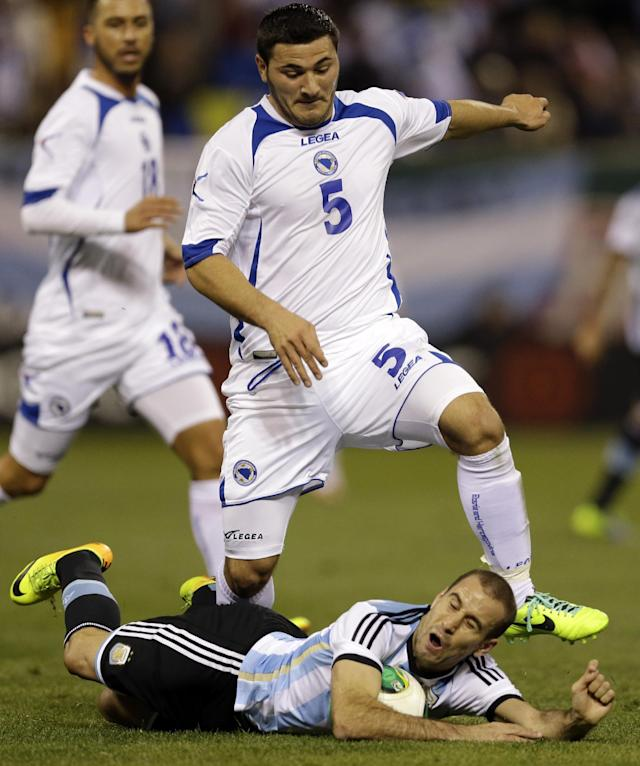 Bosnia's Sead Kolasinac (5) leaps over Argentina's Rodrigo-Palacio, bottom, during the first half of an international friendly soccer match Monday, Nov. 18, 2013, in St. Louis. (AP Photo/Jeff Roberson)