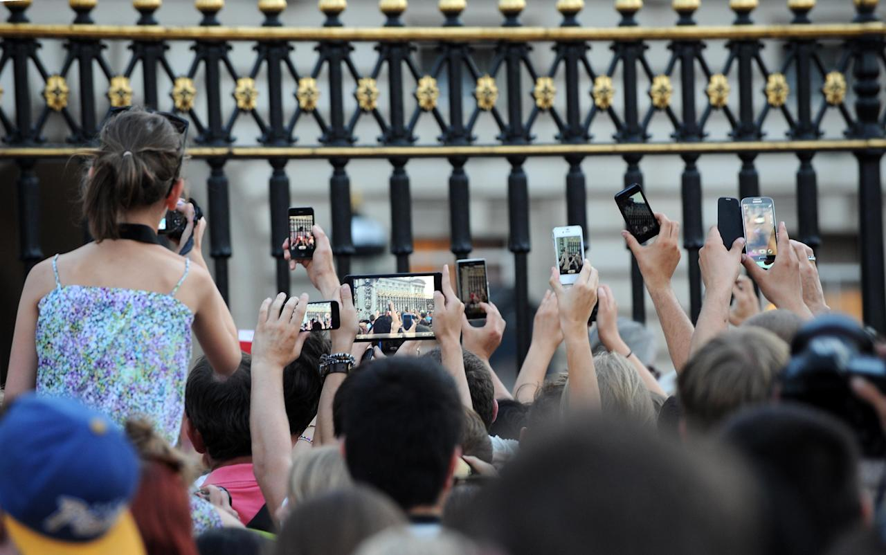 Members of the public try to take photos of an easel in the Forecourt of Buckingham Palace with the notification, to announce the birth of a baby boy, at 4.24pm to the Duke and Duchess of Cambridge at St Mary's Hospital in west London.