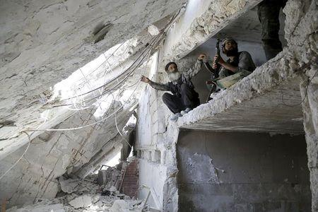 Rebel fighters from the Ahrar al-Sham Islamic Movement take positions inside a building in Jabal al-Arbaeen, which overlooks the northern town of Ariha, one of the last government strongholds in the Idlib province May 26, 2015. REUTERS/Khalil Ashawi