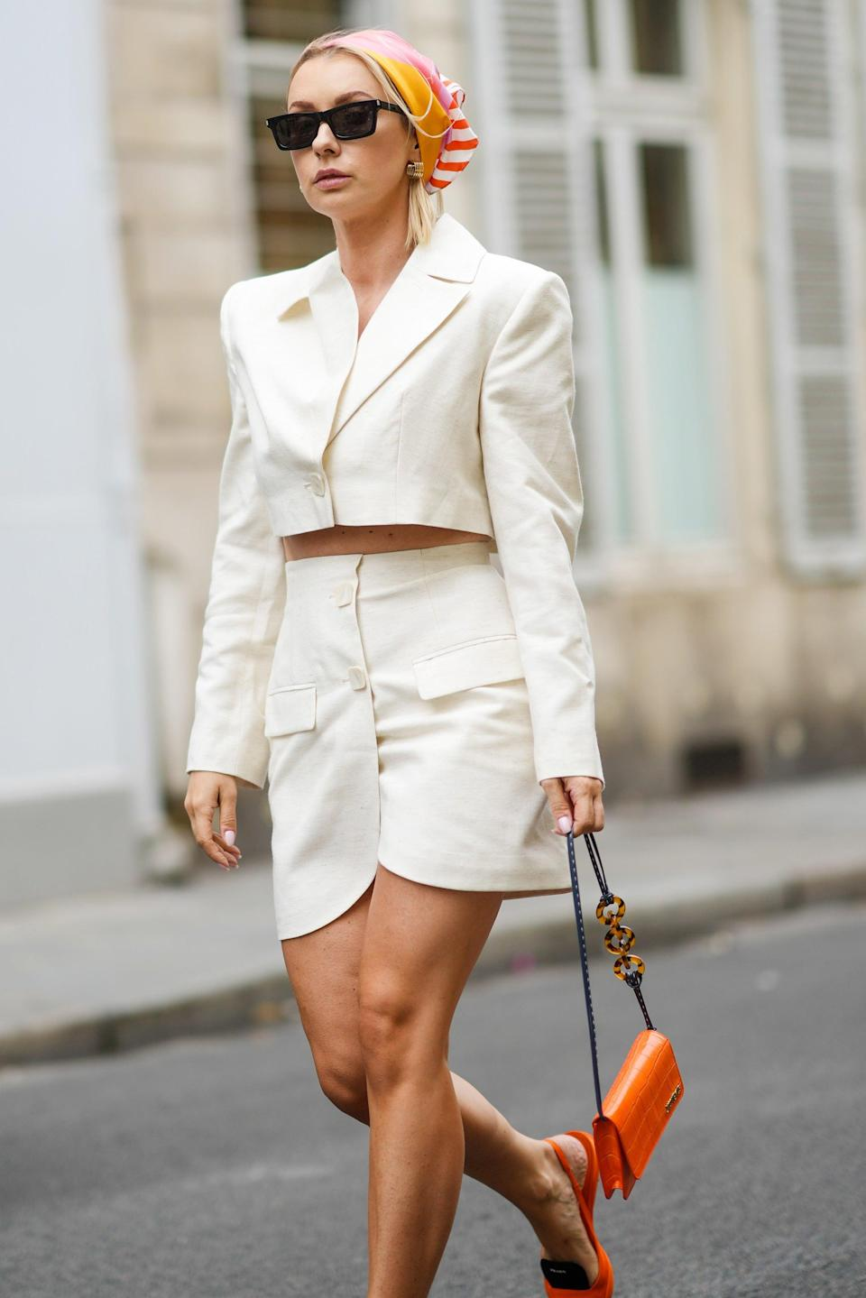 """Influencer Justyna Czerniak brought some summer fun with her accessories, pairing her white two-piece set with an orange-and-pink scarf, bag, and shoes. <span class=""""copyright"""">Photo: Edward Berthelot/Getty Images.</span>"""