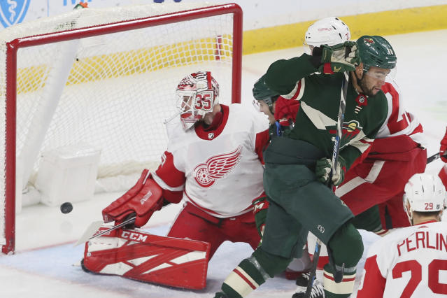 Minnesota Wild's Jordan Greenway, right, skates away after scoring against Detroit Red Wings' goalie Jimmy Howard, left, in the first period of an NHL hockey game Wednesday, Jan. 22, 2020, in St. Paul, Minn. (AP Photo/Jim Mone)