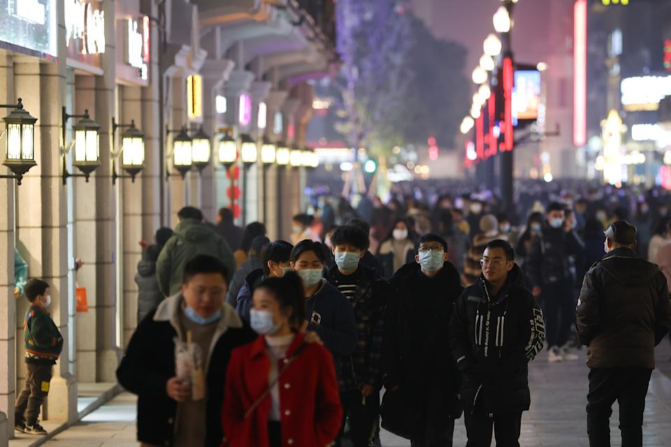 WUHAN, CHINA - JANUARY 26:  Citizens wear face masks as they walk on the commercial street on January 26, 2021 in Wuhan, China. In order to curb the spread of the new crown pneumonia COVID-19 disease, the Chinese government closed the city of Wuhan for 76 days starting January 23, 2020.  (Photo by Lintao Zhang/Getty Images)