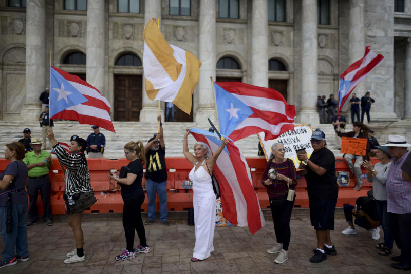 People join a protest organized by Puerto Rican singer Rene Perez of Calle 13 over emergency aid that until recently sat unused in a warehouse amid ongoing earthquakes, in San Juan, Puerto Rico, Thursday, Jan. 23, 2020. Protesters demanded the ouster of Gov. Wanda Vázquez. (AP Photo/Carlos Giusti)