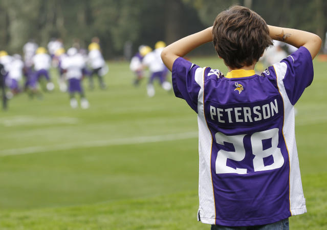 A boy wearing a Minnesota Vikings' Adrian Peterson shirt watches the team practice their football at the Grove Hotel in Watford, England, Wednesday, Sept. 25, 2013. Vikings play Pittsburgh Steelers on Sunday in a NFL football game at Wembley Stadium in London. (AP Photo/Sang Tan)