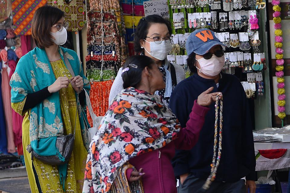 Tourist wearing facemasks as a preventative measure against the COVID-19 coronavirus, walk along a market area in New Delhi on February 12, 2020. - The death toll from China's coronavirus epidemic climbed past 1,100 on February 12 but the number of new cases fell for a second straight day, raising hope the outbreak could peak later this month. (Photo by Sajjad HUSSAIN / AFP) (Photo by SAJJAD HUSSAIN/AFP via Getty Images)