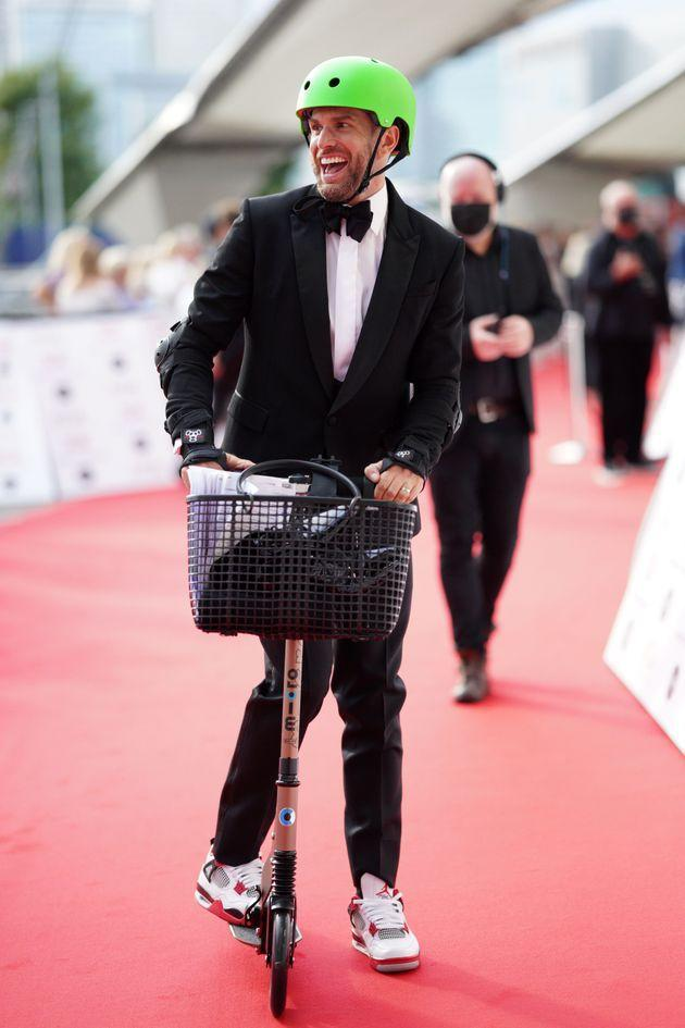 Joel looked somewhat more comfortable on the scooter as he made it further down the red carpet (Photo: Scott Garfitt/Shutterstock)