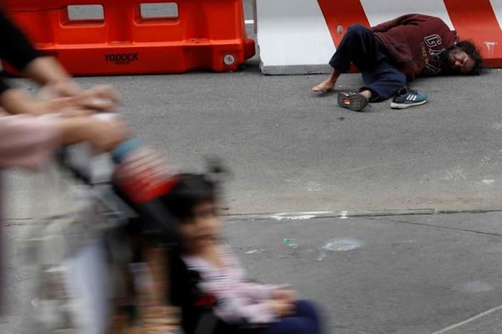 A man lays on the street outside Pennsylvania Station transit hub in New York City