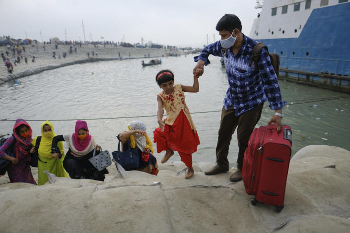 A man holds a child's hand as thousands of people leaving for their native places to celebrate Eid-al-Fitr rush to the Mawa ferry terminal ignoring risks of coronavirus infection in Munshiganj, Bangladesh, Thursday, May 13, 2021. (AP Photo/Mahmud Hossain Opu)