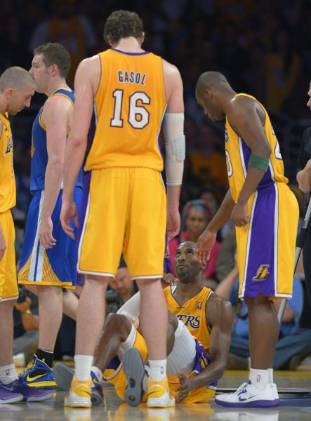 Los Angeles Lakers guard Kobe Bryant, second from right, looks up sat Pau Gasol, of Spain, and guard Jodie Meeks, right, after being injured during the second half of their NBA basketball game against the Golden State Warriors, Friday, April 12, 2013, in Los Angeles. The Lakers won 118-116. (AP Photo/Mark J. Terrill)
