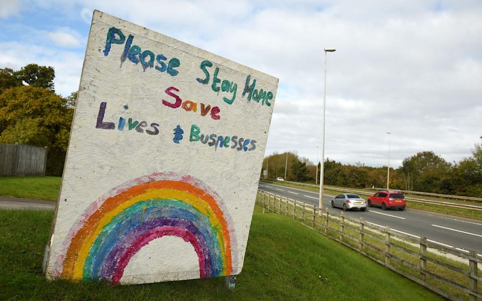 A sign by the side of a road in Flint, north Wales, urges people to stay at home during the country's new 'fire break' lockdown - Oli Scarff/AFP
