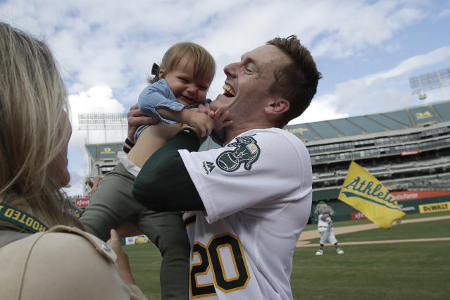 Oakland Athletics' Mark Canha (20) celebrates with his daughter Cami after the Athletics defeated the Kansas City Royals 1-0 in 11 innings a baseball game in Oakland, Calif., Wednesday, Sept. 18, 2019. Canha hit a double to score Jurickson Profar. (AP Photo/Jeff Chiu)