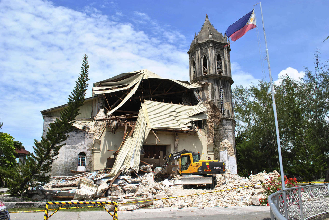 A crane shifts through the rubble of the damaged Our Lady of Assumption Parish church following a 7.2-magnitude earthquake, at Dauis in Bohol, central Philippines, Tuesday Oct. 15, 2013. The tremor collapsed buildings, cracked roads and toppled the bell tower of the Philippines' oldest church Tuesday morning, causing multiple deaths across the central region and sending terrified residents into deadly stampedes. (AP Photo)