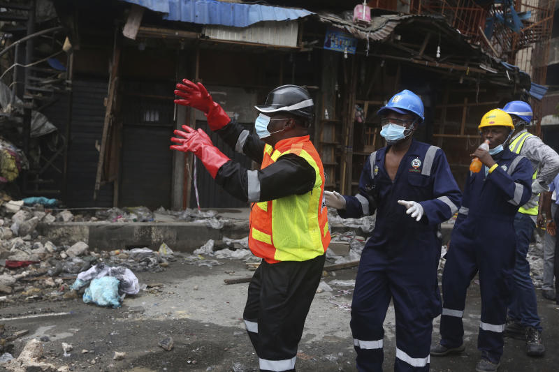 Olufemi Oke- Osanyintolu, director general of Lagos State Emergency Management Agency, left, directs a crane operator at the site of a fire in Balogun Market in downtown Lagos, Nigeria, Nov. 6, 2019. (Photo: Sunday Alamba/AP)