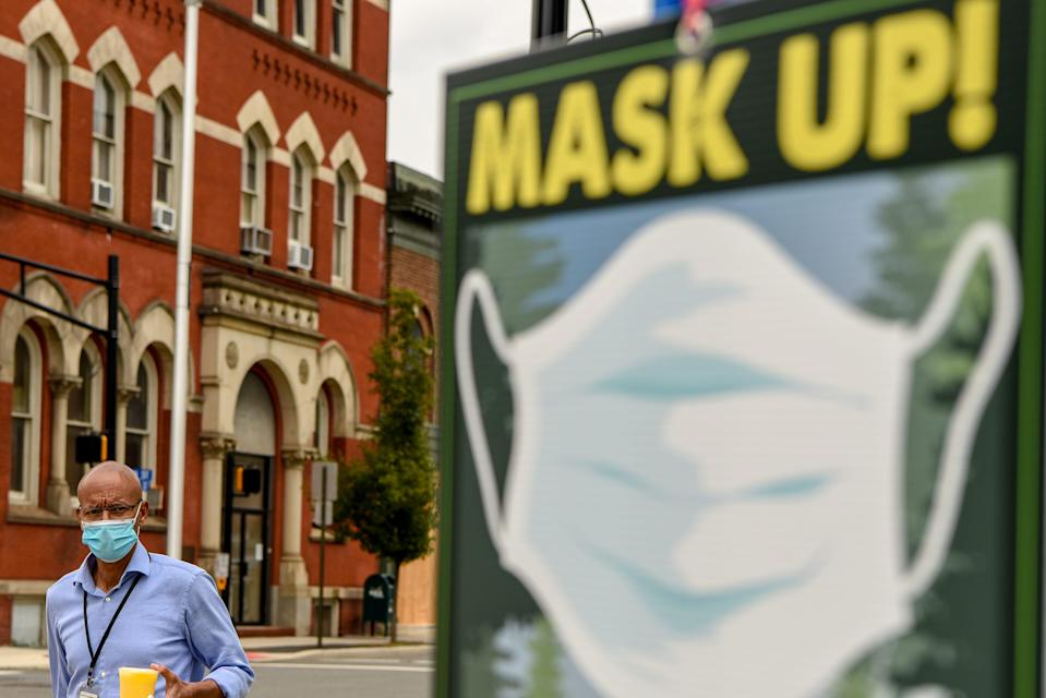 """Jorge Meneses wears a mask as he walks by a """"Mask Up"""" sign on Main Street in Hackensack on Wednesday July 8, 2020."""
