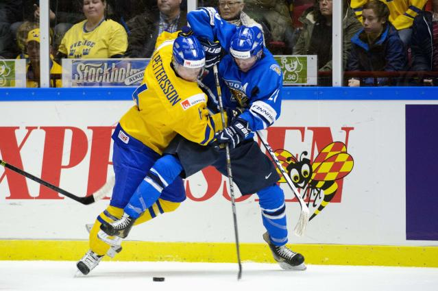 Sweden's Jesper Pettersson (L) vies with Finland's Artturi Lehkonen during their IIHF World Junior Championship Group B preliminary round ice hockey match at Malmo Arena in Malmo, December 28, 2013. REUTERS/Ludvig Thunman/TT News Agency (SWEDEN - Tags: SPORT ICE HOCKEY) ATTENTION EDITORS - THIS IMAGE HAS BEEN SUPPLIED BY A THIRD PARTY. IT IS DISTRIBUTED, EXACTLY AS RECEIVED BY REUTERS, AS A SERVICE TO CLIENTS. SWEDEN OUT. NO COMMERCIAL OR EDITORIAL SALES IN SWEDEN. NO COMMERCIAL SALES